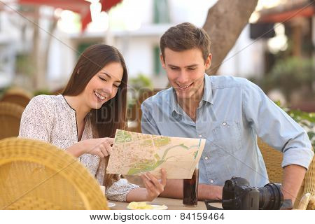 Couple Tourists Consulting A Guide In A Restaurant