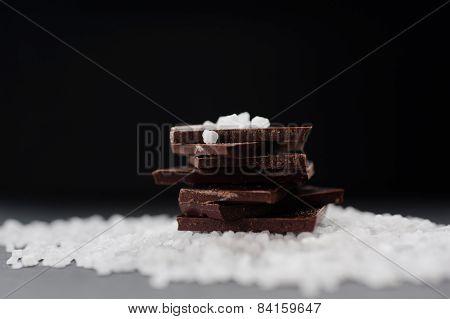 Pile of dark bitter chocolate with sea salt on dark background