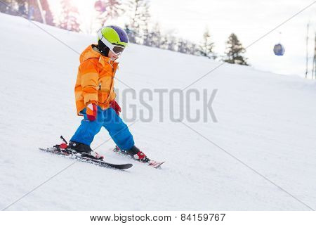 Skiing boy in ski mask, helmet on mountain slope
