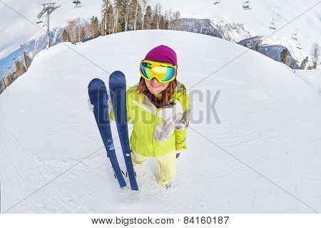 Smiling young woman in ski mask on snow mountains