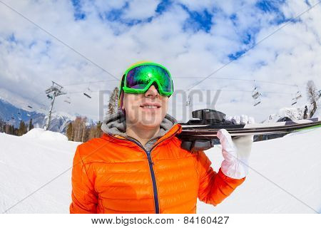 Smiling young man wearing mask holds ski in winter