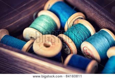 Collection Of Pink Spools Threads Arranged In A Grunge Wooden Box