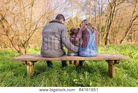 Man and woman hugging little girl sitting on a bench