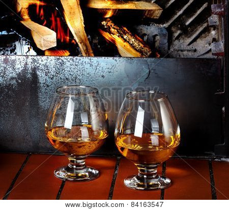 Two Tanks Of Cognac On The Old Brick Fireplace With A Bright Fire