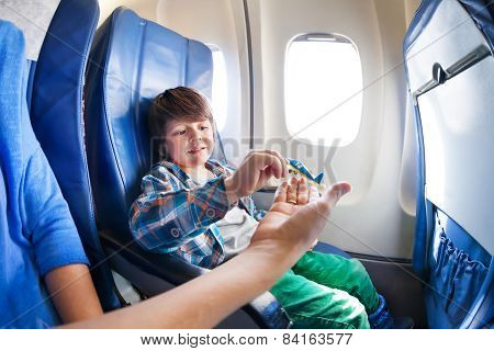 Boy play with mother in jet plane seat