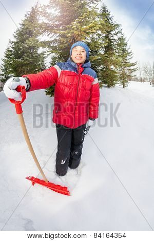 Arabian boy with shovel in winter during day