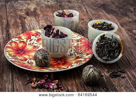 Variety Of Dry Tea Leaves In Jade Stacks On Wooden Background