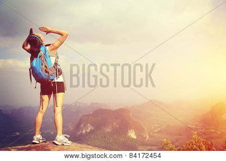 young woman hiker yelling at mountain peak