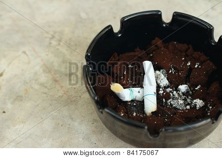 Cigarette In The Ashtray On The Cement Floor.