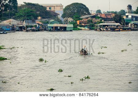 Woman on boat floating down Mekong river