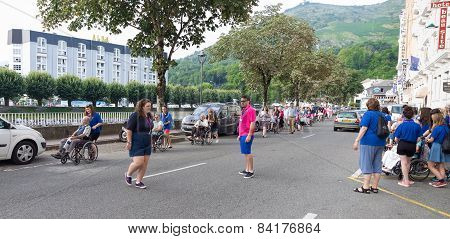 Helpers And Pilgrims Moving Down Avenue Peyramale In Lourdes