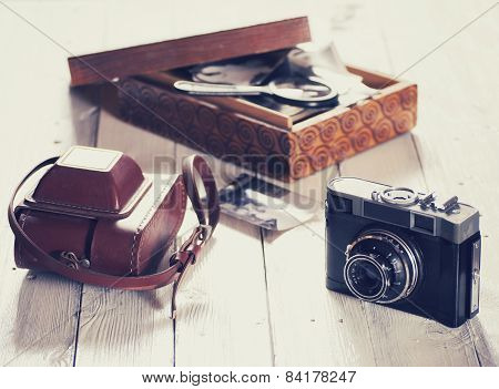 Old camera with bag and wood box with photos