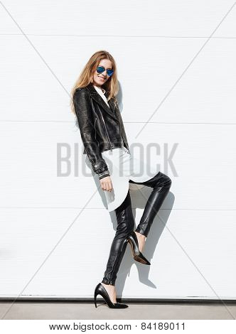 oung beautiful fashionable woman in leather jacket on high heels