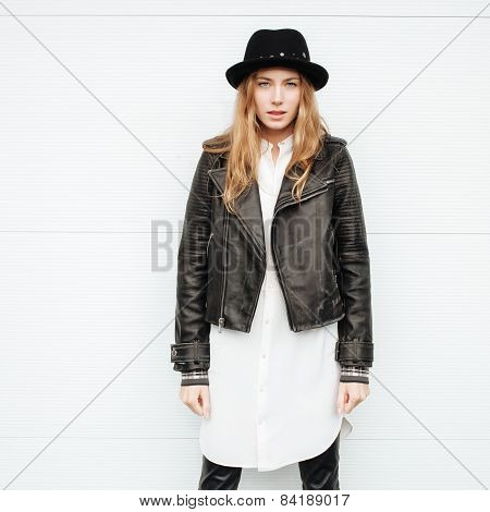 Young beautiful fashionable woman in leather jacket and hat outdoors