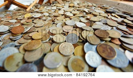 Many different old coins in a dish
