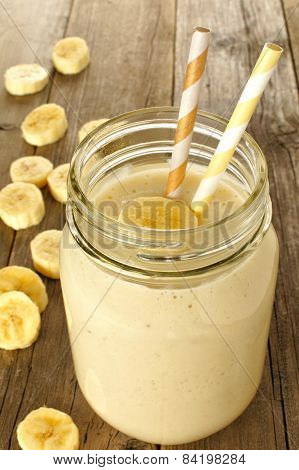 Banana smoothie in jar on wood