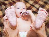 stock photo of naked children  - beautiful little baby drinking tea or juice from bottle - JPG