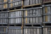 stock photo of wooden crate  - several old wooden fruit crates stacked near warehouse - JPG