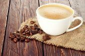 stock photo of brew  - white cup brewed coffee costs on sacking on wooden table background - JPG