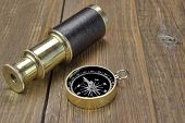 picture of spyglass  - Vintage Compass And Spyglass on Grunge Wooden Board Close - JPG