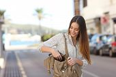 stock photo of casual wear  - Casual happy woman walking on the street and searching something in a bag - JPG