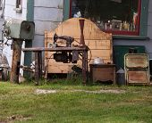 pic of junk-yard  - Assortment of junk and items on a front lawn - JPG