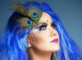 stock photo of female peacock  - Portrait of a Woman in Blue Wig and Peacock Feathers - JPG