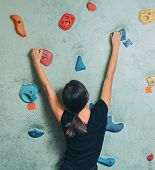 stock photo of climbing wall  - Young sporty woman climbing up on rock wall in gym - JPG