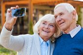 picture of bonding  - Happy senior couple bonding to each other and making selfie while standing outdoors - JPG