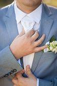 image of coat tie  - hands of groom in blue suit tying the necktie - JPG