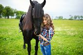 pic of beautiful horses  - Young beautiful girl with frisian horse standing in the meadow at summer time - JPG