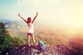 stock photo of cheers  - cheering woman hiker open arms at mountain peak - JPG