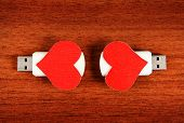 foto of usb flash drive  - Two USB Flash Drive with Heart Shapes on the Wooden Background - JPG