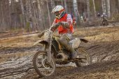 image of motocross  - Motocross driver on muddy offroad track and wet terrain at cross country competition in Parola Finland - JPG