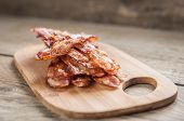 stock photo of strip  - Stack Of Fried Bacon Strips On The Wooden Board - JPG