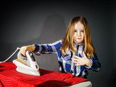 pic of cinderella  - Cute little girl helping your mother by ironing clothes childhood concept - JPG