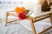 stock photo of bed breakfast  - Closeup photo of tray with breakfast and red rose on bed at hotel room - JPG