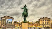 stock photo of versaille  - Statue of Louis XIV in front of the Palace of Versailles near Pairs