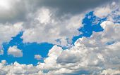 image of cumulus-clouds  - White cumulus clouds against a bright blue sky on a sunny day - JPG