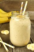 picture of masonic  - Banana oatmeal breakfast smoothie in mason jar with straws on wood table - JPG