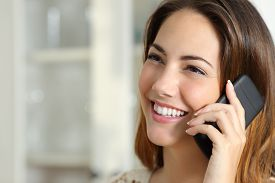 stock photo of self-employment  - Close up portrait of a happy woman talking on the mobile phone at home - JPG
