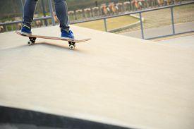 picture of skateboard  - young skateboarder legs skateboarding at skatepark ramp  - JPG