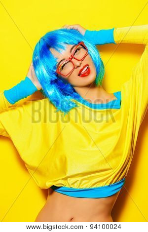 Bright glamorous girl in vivid clothes and a wig alluring over yellow background. Beauty, fashion. Cosmetics, hairtsyle. Optics, eyewear.