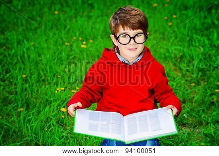 Cute 7 years old boy sitting on a grass and reading a book. Summer day.