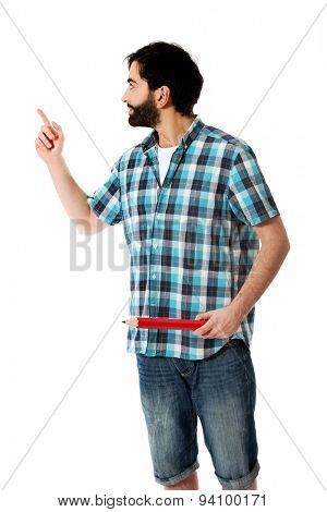 Young man holding oversized red pencil, pointing up.