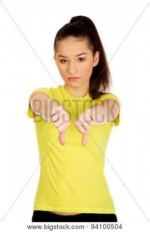 Young unhappy student woman showing thumbs down.