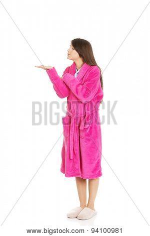 Beautiful woman wearing pink bathrobe showing empty palm.