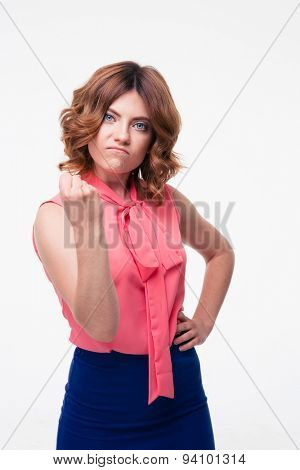Aggressive young woman showing her fist isolated on a white background. Looking at camera