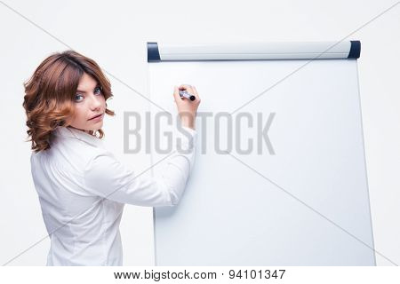Businesswoman presenting strategy on a blank flipchart isolated on a white background. Looking at camera