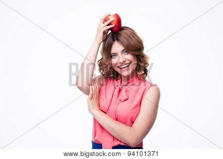 Cheerful woman holding apples on head isolated on a white background